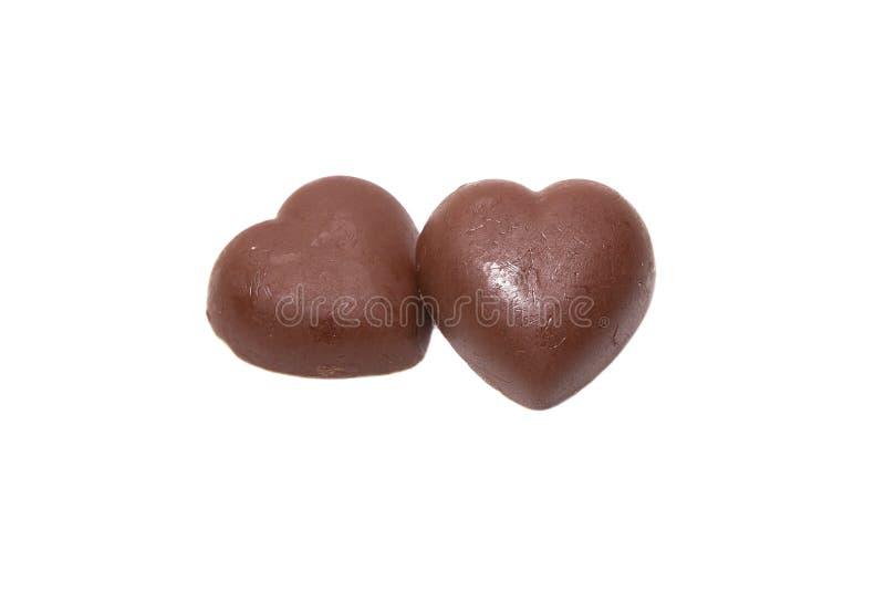 Twee chocoladeharten op witte achtergrond stock afbeeldingen