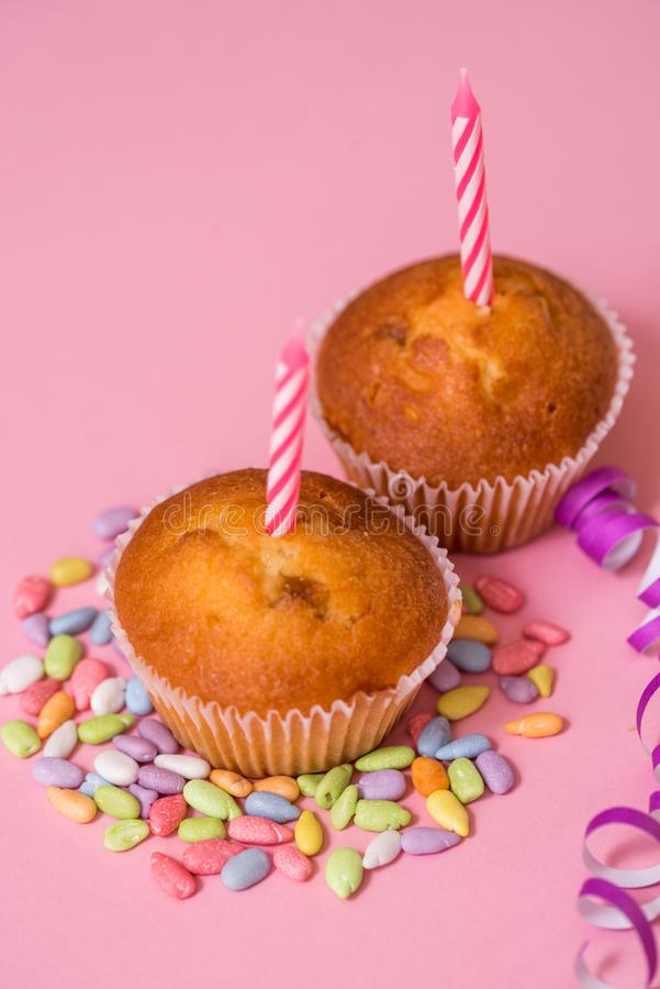 twee chocolademuffins, een verjaardagskaars Partij voor meisjes Kappen en klatergoud en multi-colored snoepjes op een roze achter royalty-vrije stock foto's