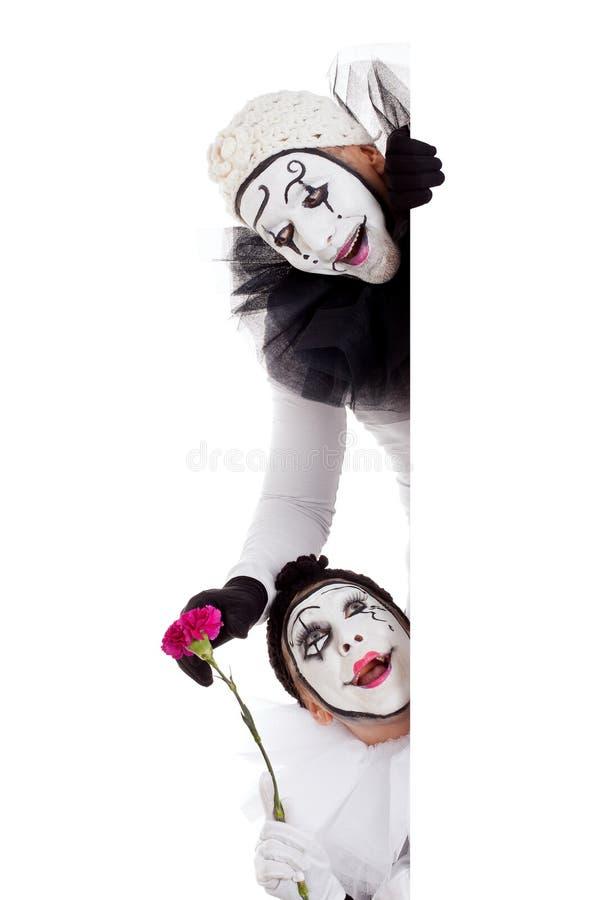 Twee clowns die in liefde rond een grens kijken stock fotografie