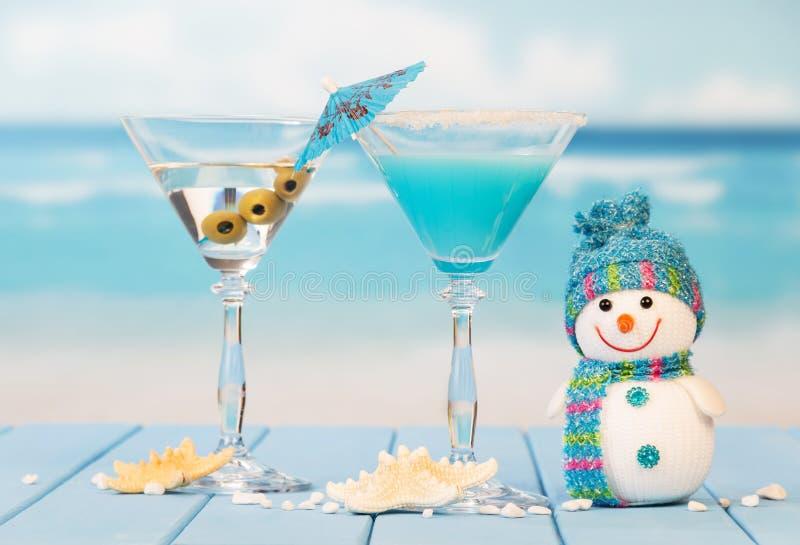 Twee cocktails, olijven, sterren en sneeuwman op overzeese achtergrond royalty-vrije stock foto