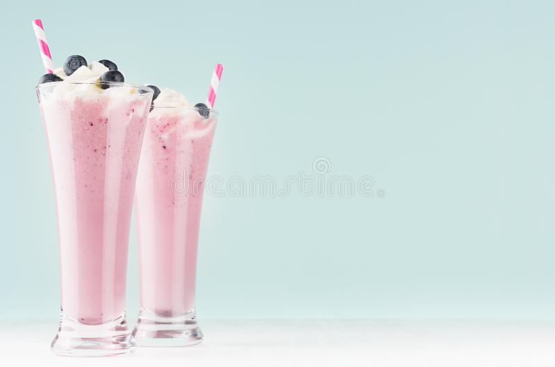 Twee cocktails van de bosbessenmelk in elegant glas met stro, bessen, slagroom in zacht licht munt groen binnenland, exemplaarrui royalty-vrije stock afbeeldingen