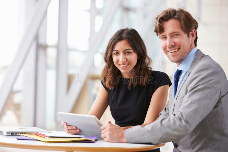 Twee collectieve bedrijfscollega's die op het werk aan camera glimlachen stock afbeeldingen