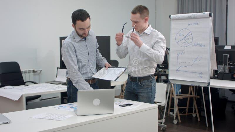 Twee collectieve stafmedewerkers die bedrijfsbespreking in bureau hebben stock foto's
