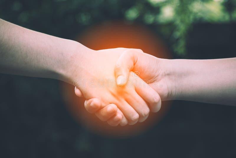 Twee collega het schudden hand met warm licht stock foto's