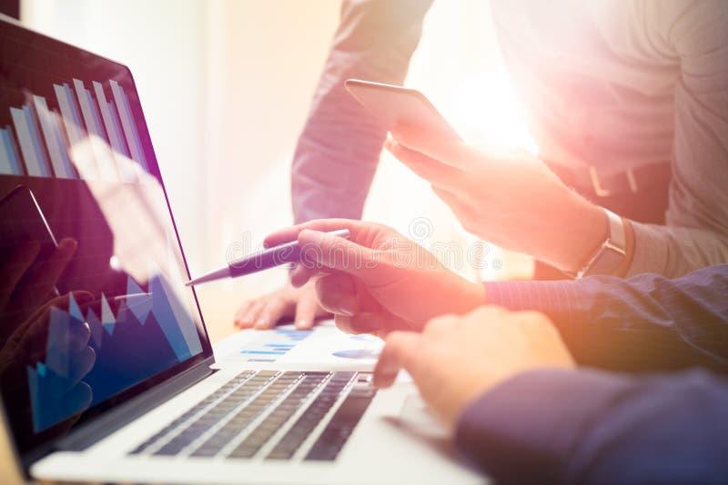 Twee collega's die aan nieuwe globale financiële strategie werken plannen het gebruiken van laptop en smartphone Moderne commerci royalty-vrije stock afbeelding