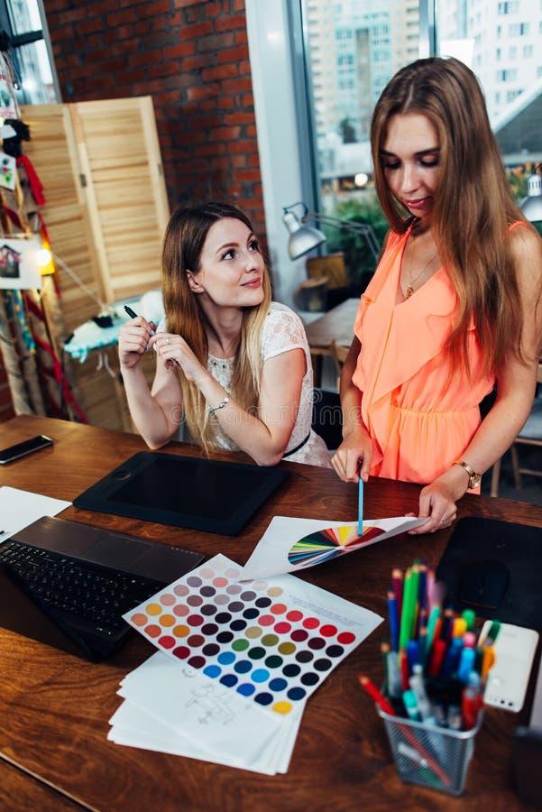 Twee collega's die creatieve ideeën delen die nieuwe ontwerpen in moderne studio bespreken royalty-vrije stock fotografie