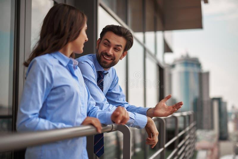 Twee collega's die op balkon van het werkbureau spreken stock foto's