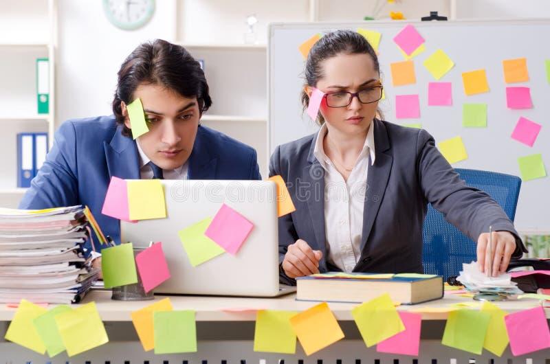 Twee collega'swerknemers die in het bureau werken stock afbeeldingen