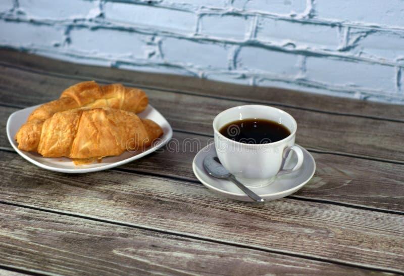 Twee croissants op een ceramische plaat en een kop van zwarte koffie op de lijst door de bakstenen muur Close-up royalty-vrije stock afbeelding