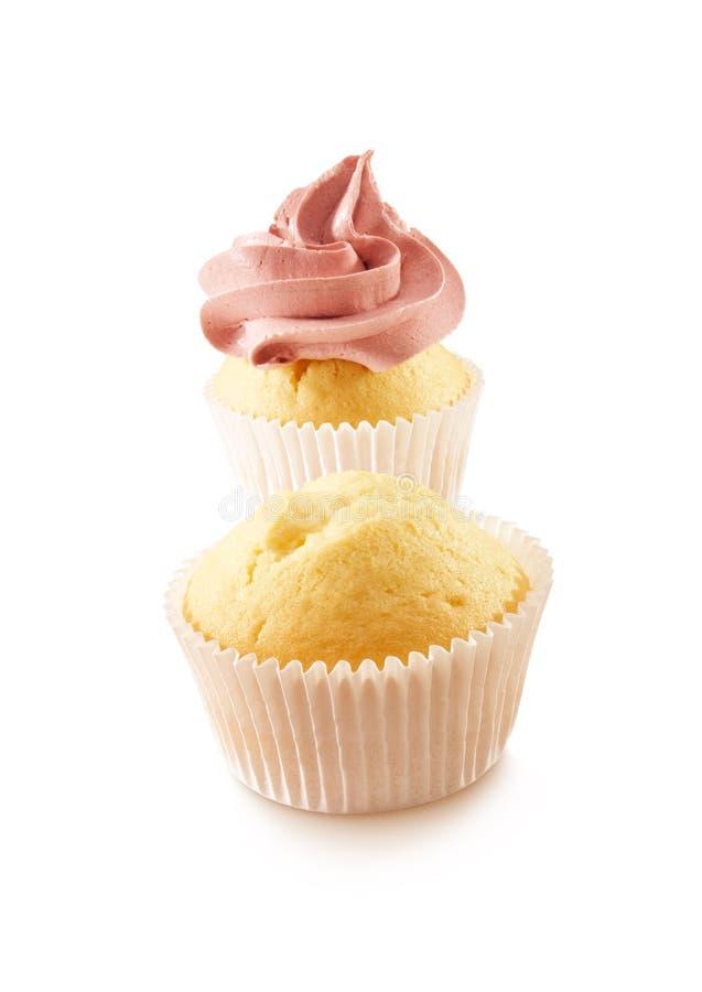 Twee cupcakes op een witte achtergrond en is verfraaid met een rode werveling stock afbeelding