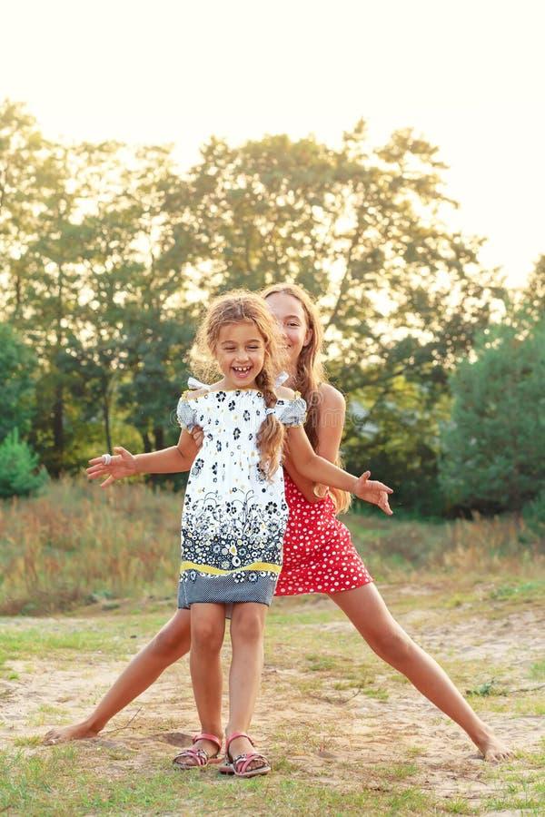 Twee Cute kleine meisjes die het platteland omarmen en lachen Het concept van vrolijke kinderen in de openlucht stock foto