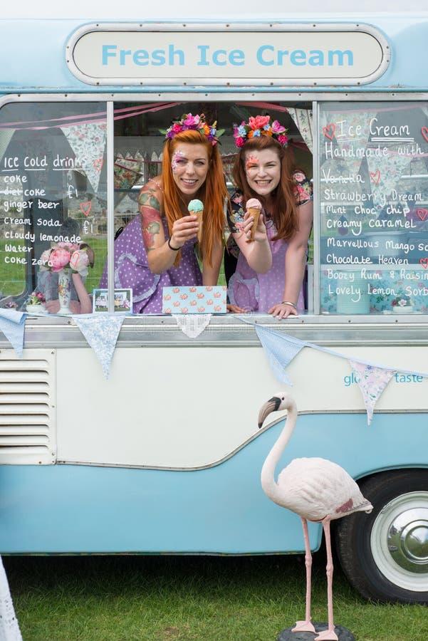 Twee dames die roomijs in bestelwagen met flamingo houden stock afbeelding