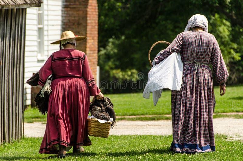 Twee dames/vrouwen die naar huis in koloniale kleding lopen royalty-vrije stock foto