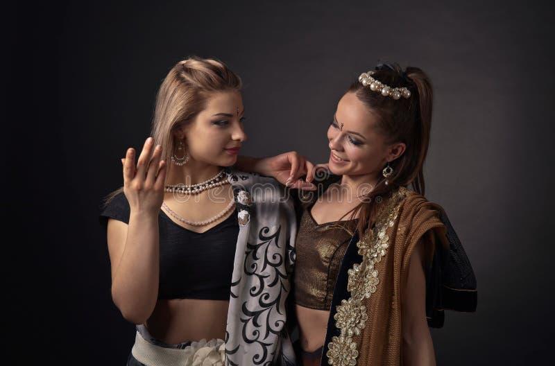 Twee dansende jonge vrouwen in het nationale Indische kostuum stock afbeeldingen