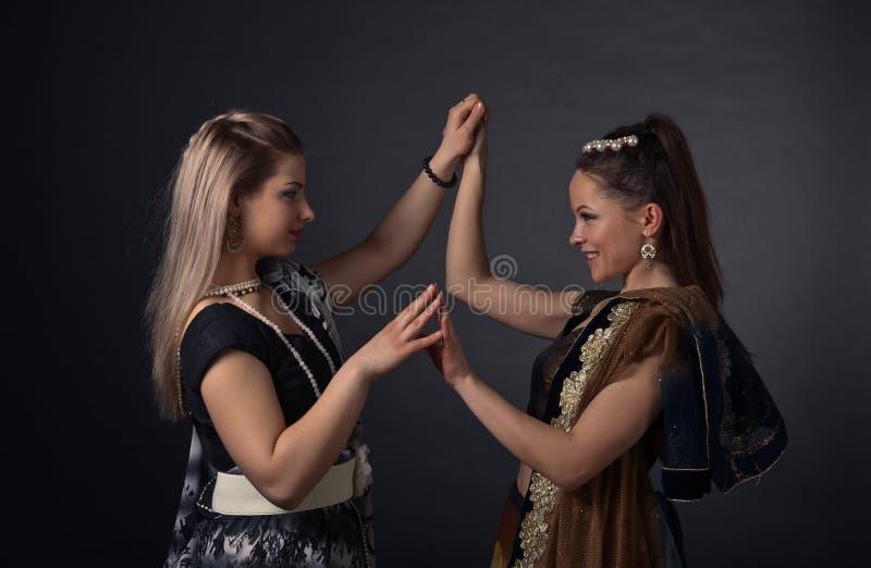 Twee dansende jonge vrouwen in het nationale Indische kostuum royalty-vrije stock afbeelding