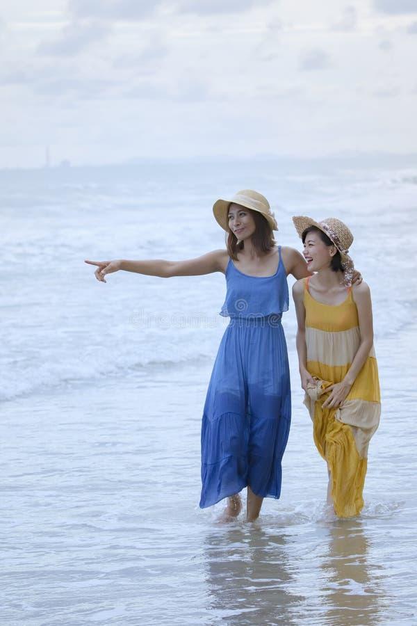 Twee de Aziatische tijd van de vrouwen ontspannende vakantie op overzees strand royalty-vrije stock foto's