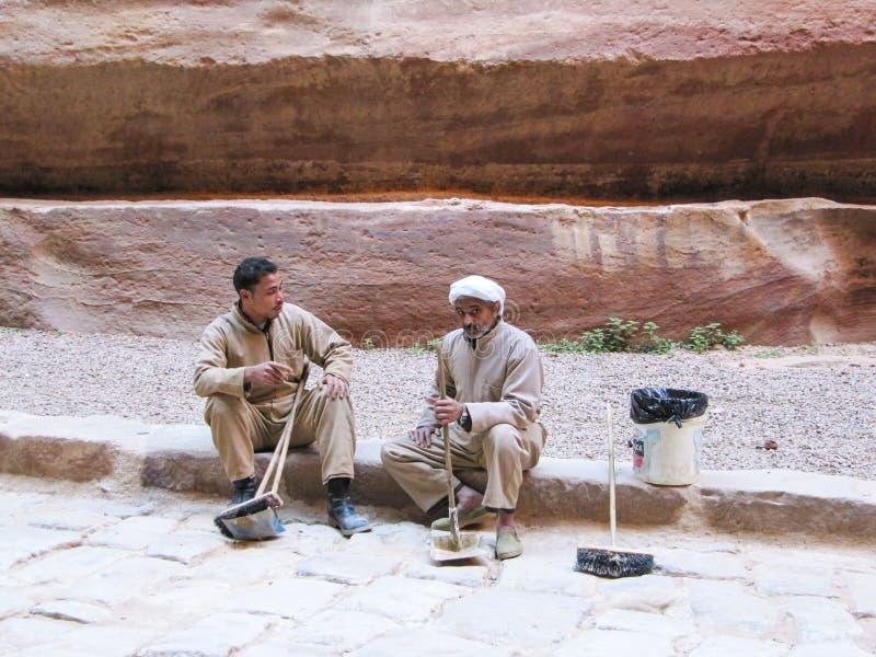 Twee de mens-reinigingsmachines hebben een rust, zittend op de Rode rotsen canion Jordanië, 26 petra-December, 2009, stock foto's