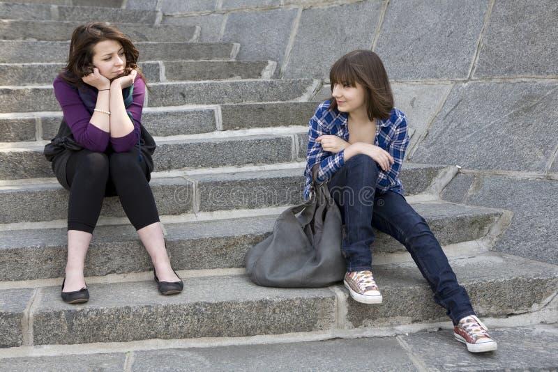 Twee de stedelijke zitting van het tienermeisje op treden royalty-vrije stock afbeelding