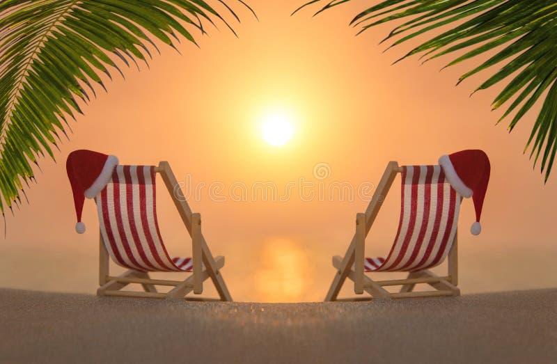 Twee deckchairs met de rode hoeden van de Kerstmiskerstman bij het oceaan zandige strand van de palmzonsondergang royalty-vrije stock foto