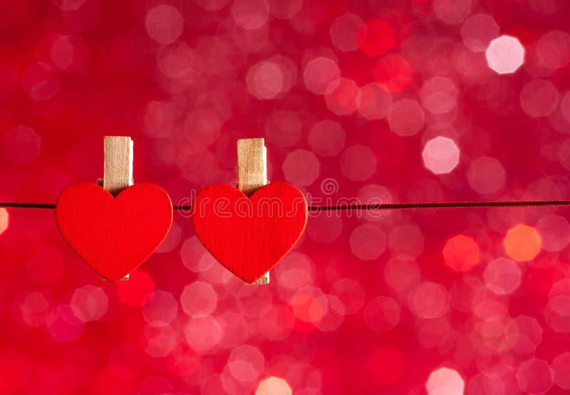Twee decoratieve rode harten die tegen rood licht bokeh achtergrond hangen, concept valentijnskaartdag royalty-vrije stock foto