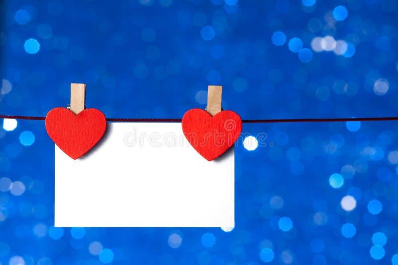 Twee decoratieve rode harten met groetkaart het hangen op blauwe lichte bokehachtergrond, concept valentijnskaartdag stock foto's