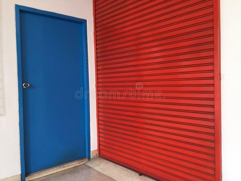 Twee deuren naast elkaar, Kleine blauwe houten deur voor mensen om grote rode metaaldeur voor groot materiaal te gebruiken royalty-vrije stock foto