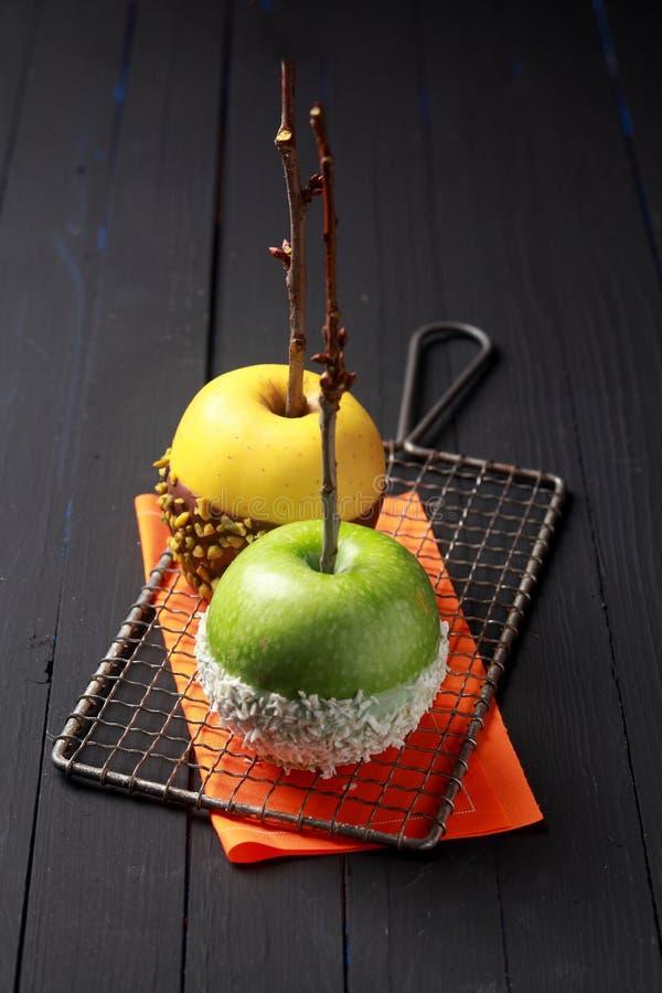 Twee die appelen in suikergoed voor een Halloween-partij worden ondergedompeld stock afbeeldingen