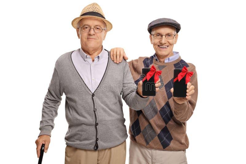 Twee die bejaarden met telefoons met rode linten worden verpakt zoals voorstelt royalty-vrije stock foto's