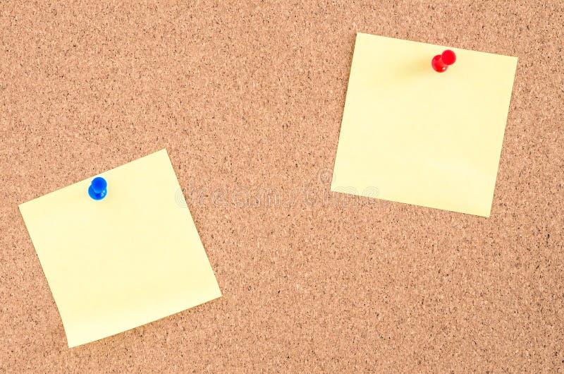 Twee die Bladen van Document aan een Noticeboard worden gespeld stock foto's