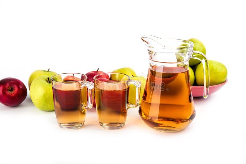 Twee die glazen en een kruik appelsap, op witte backgro wordt geïsoleerd stock afbeelding