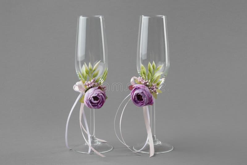 Twee die glazen van de huwelijkswijn met purpere bloemen worden verfraaid royalty-vrije stock foto
