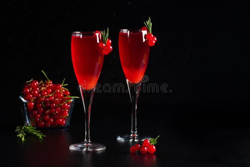 Twee die glazenredcurrant de wijn drinkt sap met rozemarijn wordt verfraaid royalty-vrije stock foto's