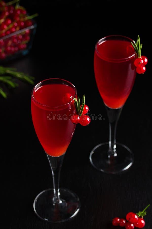Twee die glazenredcurrant de wijn drinkt sap met rozemarijn wordt verfraaid stock foto
