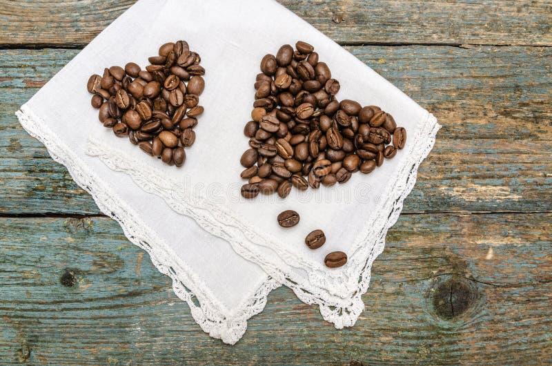 Twee die harten van koffiebonen worden gemaakt op houten achtergrond royalty-vrije stock afbeelding