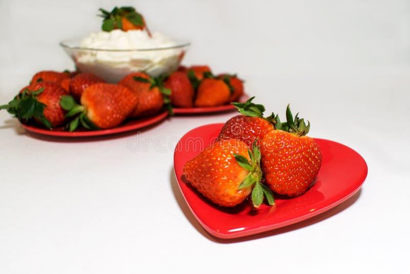 Twee die hartplaten met aardbeien worden gevuld stock afbeeldingen