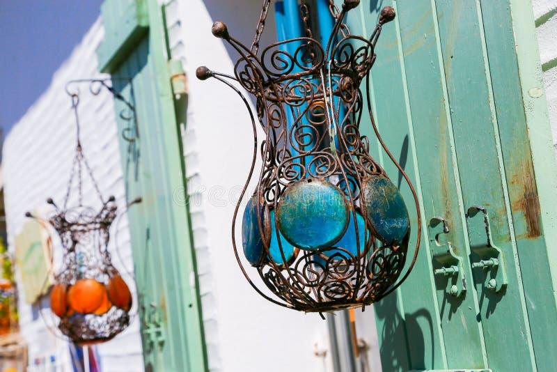 Twee die lampen van draad het filigraan hangen van groene blinden buiten een wit gebouw worden gemaakt royalty-vrije stock afbeelding