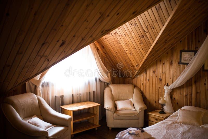 Twee die leunstoelen dichtbij het venster in een hotelruimte van hout wordt gemaakt Binnenland van een houten ruimte stock foto's
