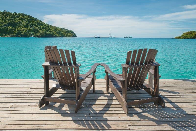 Twee die ligstoelen op houten vloer bij de overzeese mening worden geplaatst royalty-vrije stock foto