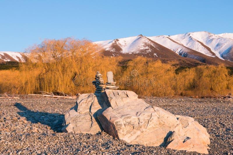 Twee die piramides van stenen bovenop twee grote rotsen worden gebouwd stock foto