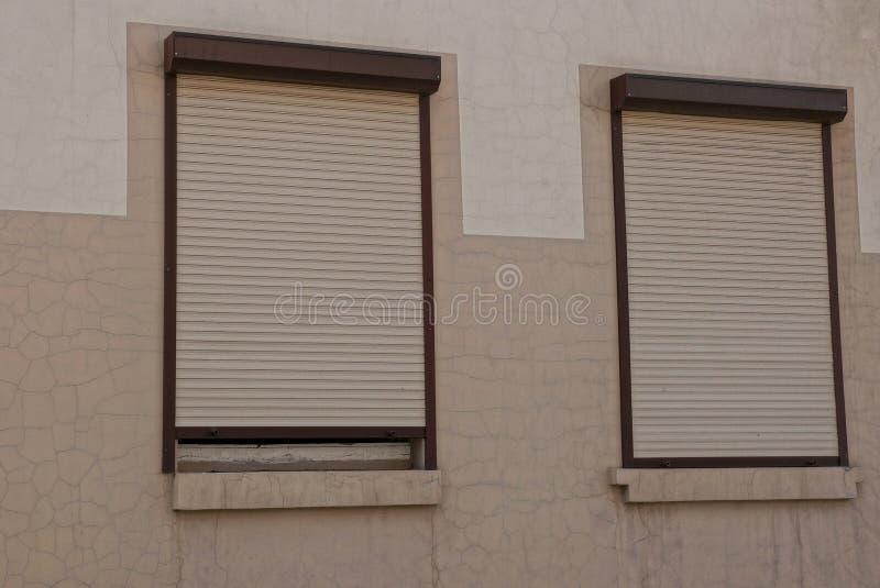 Twee die vensters door rolblinden worden gesloten op een bruine muur royalty-vrije stock fotografie