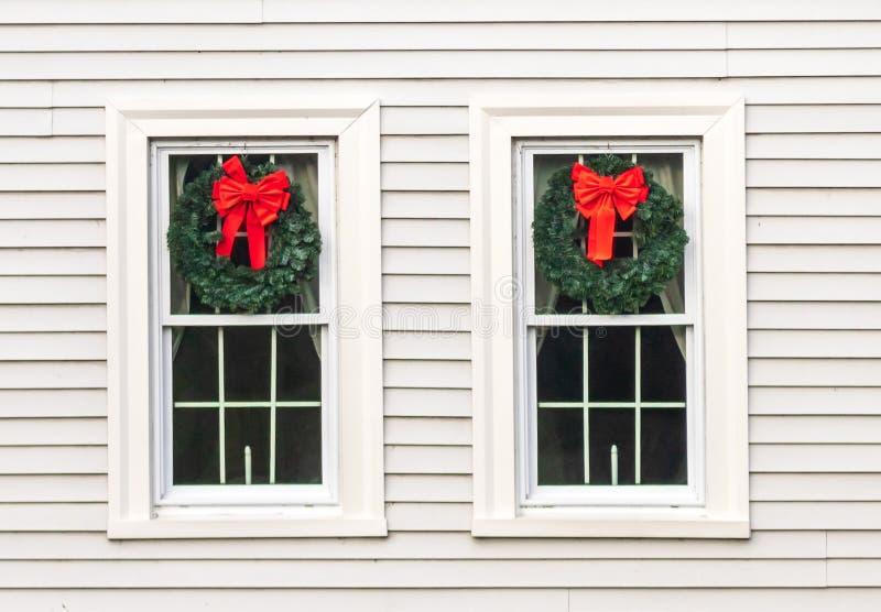 Twee die vensters met Kerstmiskronen worden verfraaid royalty-vrije stock afbeeldingen