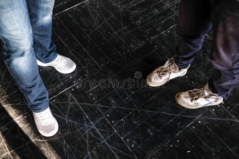 Twee die zich op de vloer, schoenen bevinden stock afbeelding