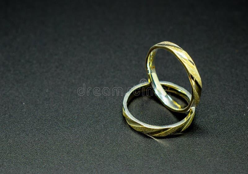 Twee die zilver en gouden bruiloftringen op een zwarte achtergrond worden geïsoleerd royalty-vrije stock foto