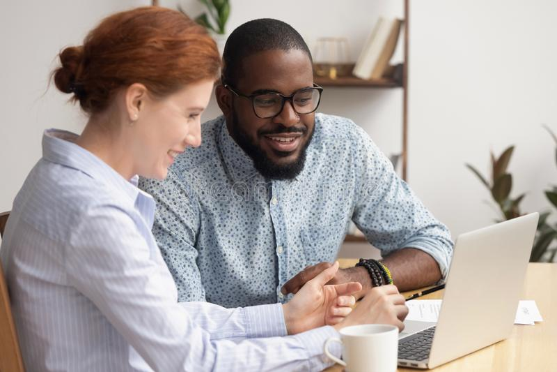 Twee divers lachend zakenlui die op grappige video op laptop letten stock foto's