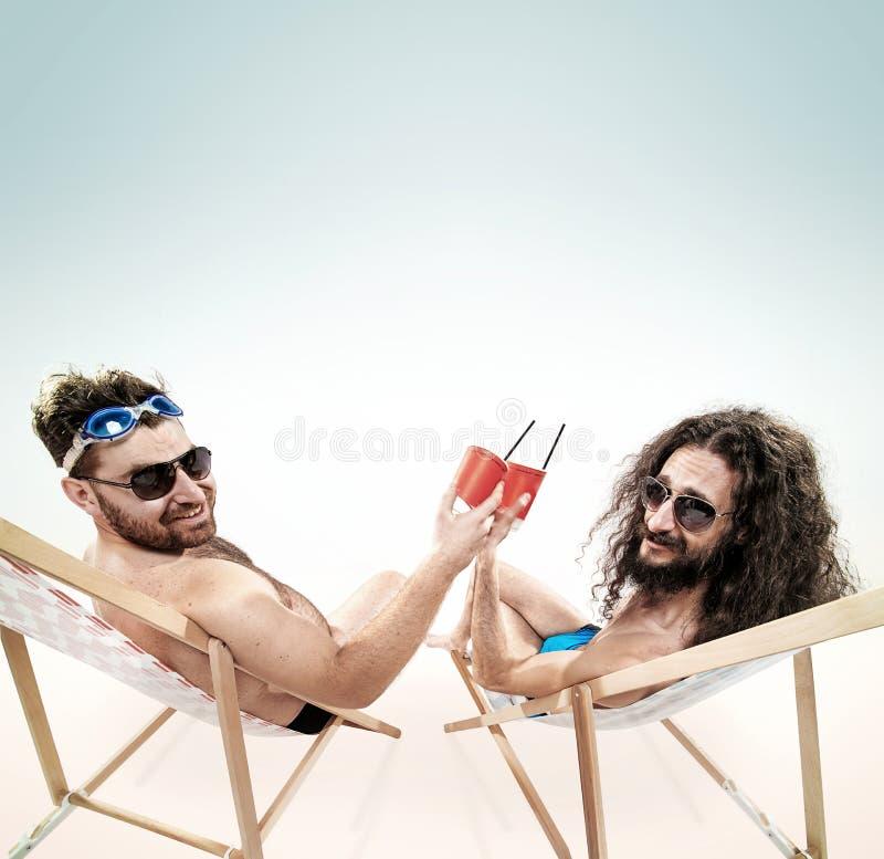 Twee diverse kerels die samen op het strand rusten royalty-vrije stock foto's