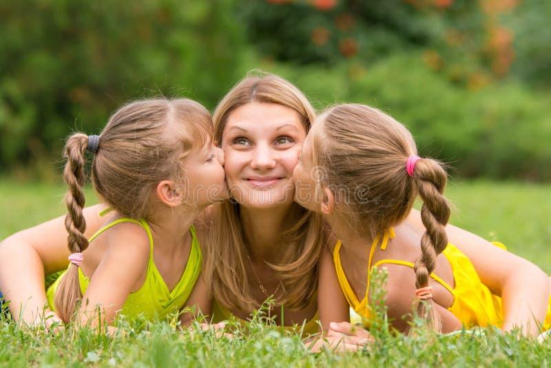 Twee dochters die moeder kussen die op gras op een picknick liggen, Moeder keken op pret stock foto's