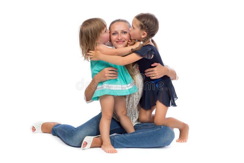Twee dochters kussen mamma stock fotografie
