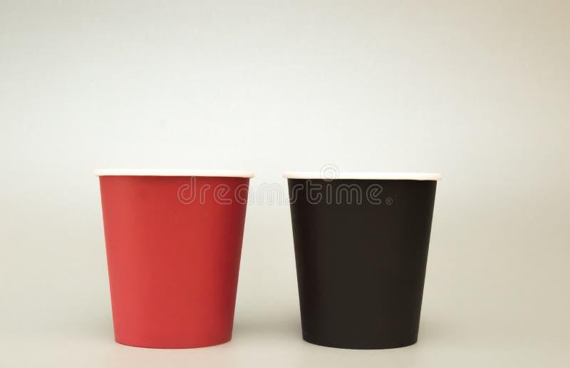 Twee document glazen voor koffie bevinden zich op een licht achtergrond, een zwarte en een rood stock foto's