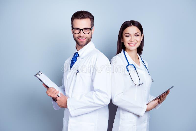 Twee dokterscollega's in witte lagen op zuivere achtergrond, het houden royalty-vrije stock afbeelding