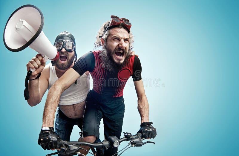 Twee dolkomische fietsers betrokken bij een wedstrijd royalty-vrije stock afbeelding